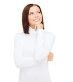 Thinking and smiling woman in white sweater Stock Images