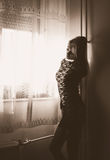 Thinking in solitude. Blond woman in mini black dress standing by the window stock photo