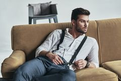 Thinking about something important. Stylishly dressed young man holding his eyewear and looking away while lying on sofa Royalty Free Stock Photo