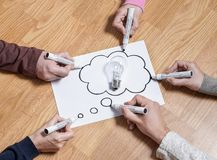 Thinking speech bubble balloon with light bulb. Brainstorming new ideas together for marketing plan or school project. Teamwork, synergy and education. Group stock photography