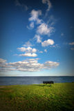 Thinking spot. Image of a bench facing the ocean on a warm summer afternoon. It's just you and the ocean. Themes: meditation, wellness, maybe retirement Stock Images