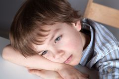Thinking student sitting at desk Royalty Free Stock Images