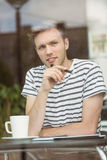 Thinking student sitting with a hot drink and holding a pen Royalty Free Stock Photo