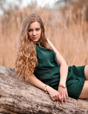 Attractive, serious, impudent, bitchy girl,woman with curly long hair. Long-haired curious,sad,laid-back person,carelessly dressed,tired,boring girl lies on tree Royalty Free Stock Image