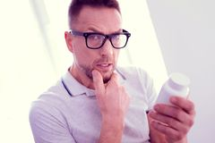Blue-eyed mature man wearing glasses thinking about taking food supplements. Thinking about supplements. Handsome blue-eyed mature man wearing glasses thinking stock photo