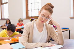 Thinking teacher sitting at desk. At the elementary school Stock Image