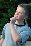 Thinking Teen. Teenage boy in a thinking pose, looking upwards, outdoors royalty free stock photography