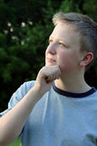 Thinking Teen 2. Portrait of a teenage boy in profile in a thinking pose, looking upward, outdoors royalty free stock image
