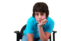 Thinking teen boy. Cute preteen brunette boy with head on hands Royalty Free Stock Photography