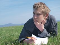 Thinking teenager. Portrait of young blond man with a pencil and blank paper (wearing grey shirt) laying in the grass in the sun Stock Images