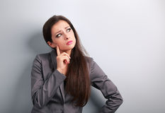 Thinking unhappy business woman in suit looking on blue empty co Stock Photo