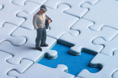 Thinking - where should I go. Plastic figure standing in front of a hole in a puzzle - looks like big problems - there is one missing part Stock Photo
