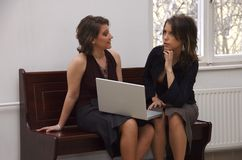 Thinking of a winning strategy. Young sexy women working together. Sitting on a bench in the court hallway, thinking of a winning strategy during the break Royalty Free Stock Images
