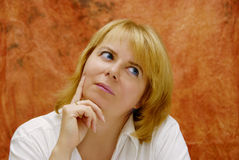 Thinking woman. Pretty blond woman with a thinking expression Stock Image
