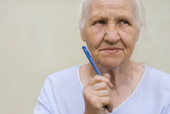 Thinking woman. Thoughtful elderly woman with pen Royalty Free Stock Photography