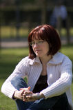 Thinking woman. Woman thinking auburn in a park Royalty Free Stock Image