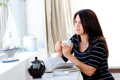 Thinking woman. Pretty caucasian woman daydreams, looking out the window with her cup of tea Stock Images