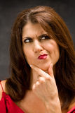 Thinking woman. The beautiful face of a thinking woman with hand on chin Royalty Free Stock Photos