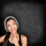 Thinking woman by blackboard. Multiracial hipster university college student pensive and contemplating looking up to the at empty blank copy space on Royalty Free Stock Images