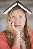 Thinking woman with book on head Stock Image
