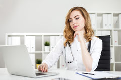 Thinking woman doctor with laptop in office Royalty Free Stock Images
