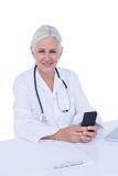 Thinking woman doctor phoning with her smartphone Royalty Free Stock Photography