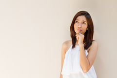 Thinking woman, facing upward on plain warm tone background. For text space Stock Image