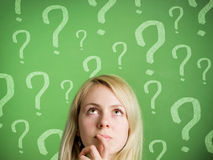 Thinking woman in front of blackboard with questio. Thinking woman in front of green blackboard with question marks. The image could symbolize many things like stock photography