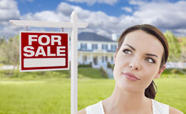 Thinking Woman In Front of House and For Sale Sign. Thoughtful Pretty Mixed Race Woman In Front of Home and House For Sale Real Estate Sign Looking Up and to the Stock Photos