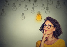 Thinking woman in glasses looking up with light idea bulb above head. Portrait thinking woman in glasses looking up with light idea bulb above head  on gray wall Royalty Free Stock Images