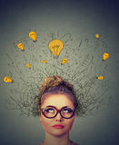 Thinking woman in glasses with question signs and light idea bulb above head looking up wondering Royalty Free Stock Images