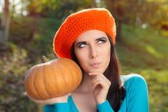Thinking Woman Holding Pumpkin in Autumn Decor Stock Photo