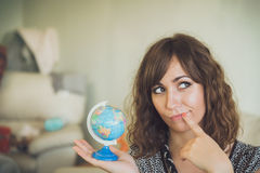 Thinking Woman Holding Small Globe in Hand Royalty Free Stock Image