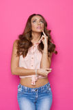 Thinking Woman Looking Up. Curious young woman in pink tied shirt and jeans looking up. Three quarter length studio shot on pink background Royalty Free Stock Image