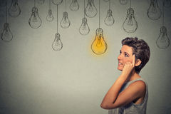 Thinking woman  looking up with light idea bulb above head Royalty Free Stock Image