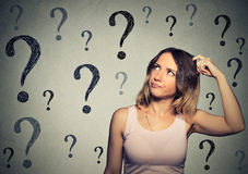 Thinking woman looking up at many questions marks. Thinking young woman looking up at many questions mark isolated on gray wall background Stock Image