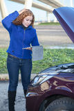 Thinking woman with opened car cowling Royalty Free Stock Photography