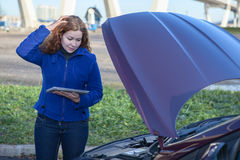 Thinking woman with opened car hood and tablet pc Stock Photos