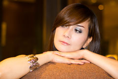 Thinking woman. With pillow seating at the sofa Stock Photo