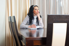 Thinking woman planning the meeting. Thinking single business woman sitting on chair at table and planning a meeting in personal agenda Royalty Free Stock Photography