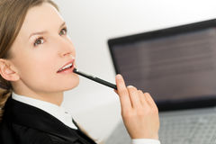 Thinking woman presenting laptop screen and pen. Bright portrait Royalty Free Stock Image