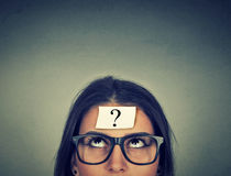 Thinking woman with question mark. On gray wall background Royalty Free Stock Photo