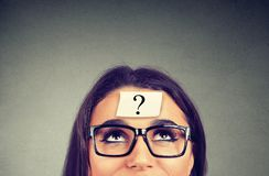 Thinking woman with question mark on gray wall background. Thinking woman in glasses with question mark looking up on gray wall background stock photography