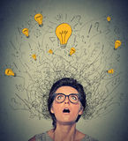 Thinking woman with question signs and light idea bulb above head looking up Stock Photo