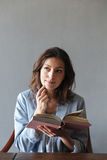 Thinking woman reading book. Stock Images