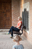 Thinking woman sitting on bench near the castle, her daughter comes to her Stock Photography
