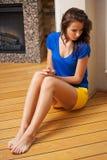 Thinking woman sitting on the floor Stock Photo