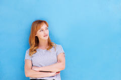 Thinking woman standing with arms crossed by blue wall. Portrait of thinking woman standing with arms crossed by blue wall Royalty Free Stock Images