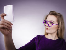 Thinking woman wearing eyeglasses holding note. Thinking business woman wearing eyeglasses holding sticky note, looking at problem solution Royalty Free Stock Images