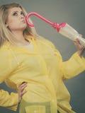 Thinking woman wearing raincoat holding closed umbrella. Preparing for rainy day. Thinking blonde woman wearing yellow raincoat holding closed umbrella Stock Image